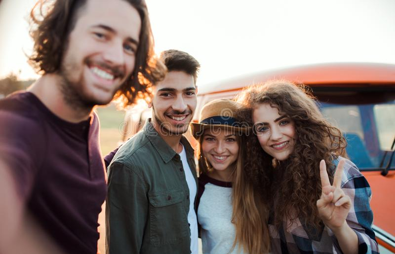 A group of young friends on a roadtrip through countryside, taking selfie. royalty free stock photography