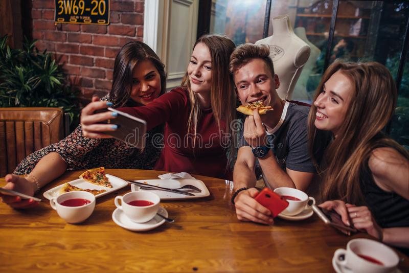 Group of cheerful young friends taking selfie with smartphone having light dinner in modern stylish restaurant stock photo