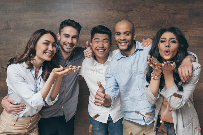 Group of cheerful young people standing together and celebrating with confetti royalty free stock images