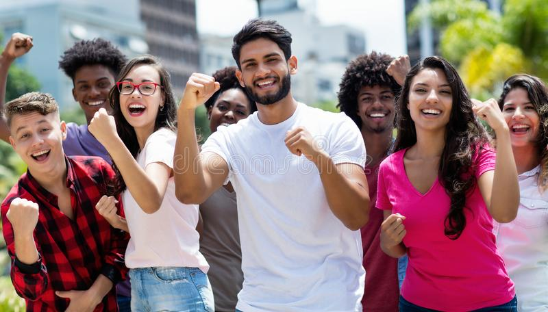 Group of cheering latin and caucasian and hispanic and african american young adults. Outdoor in summer in city stock image