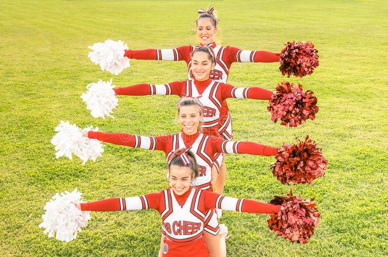 Group of cheerleaders in action with female coach. Concept of unity and team sport - Training at college high school with young happy fit teenagers stock image