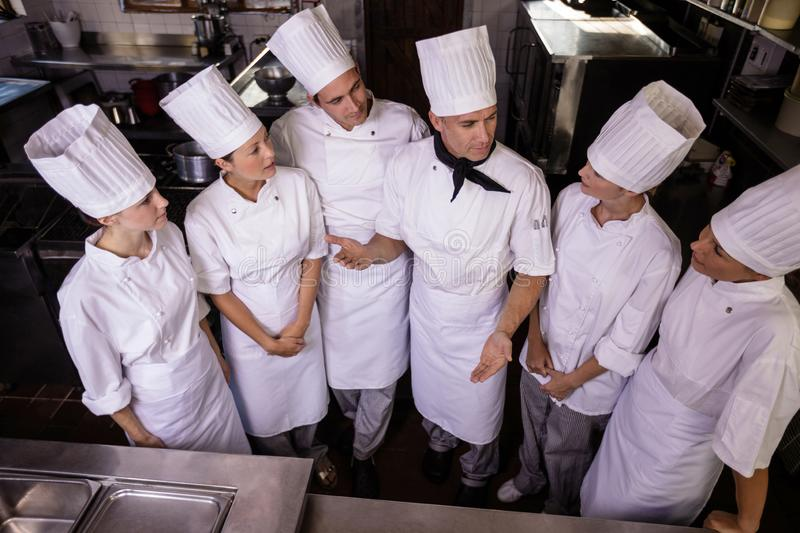Group of chefs interacting wiht each other in kitchen royalty free stock photo