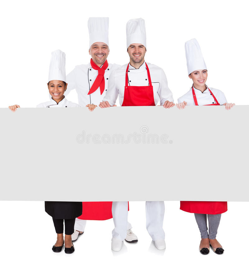 Group of chefs presenting empty banner. Isolated on white stock photography