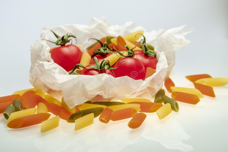 Group of cherry tomatoes and colored pasta wrapped in cooking paper stock image