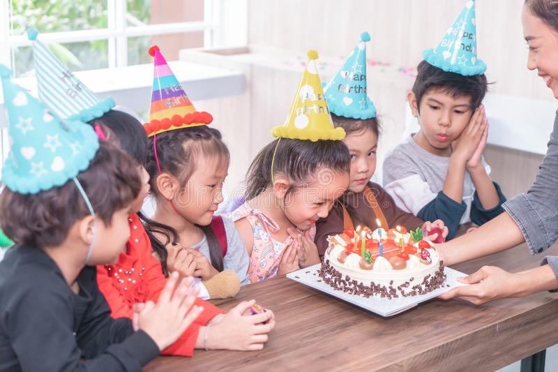 Children is blowing birthday cake in birthday party singing happy birthday. Group of children is blowing birthday cake in birthday party singing happy birthday royalty free stock photo