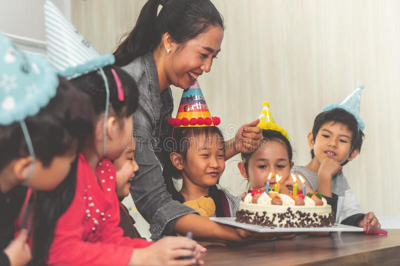 Group of children blowing birthday cake in birthday party singing happy birthday. Group of children is blowing birthday cake in birthday party singing happy royalty free stock images