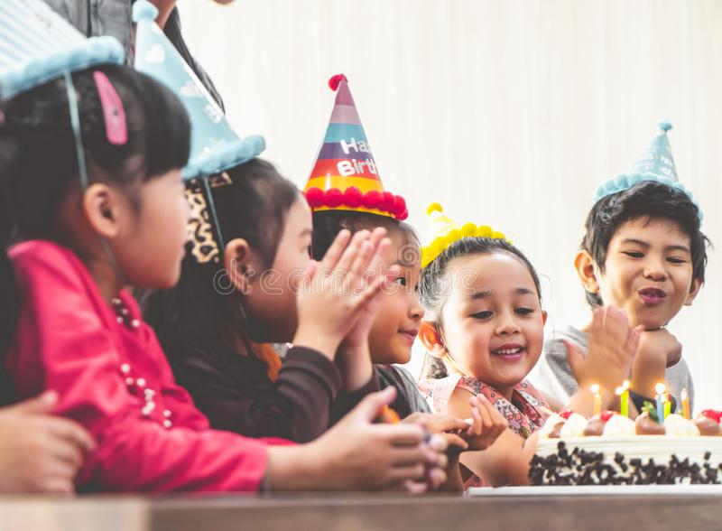 Group of children blowing birthday cake in birthday party singing happy birthday. Group of children is blowing birthday cake in birthday party singing happy stock photos