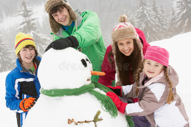 Download Group Of Children Building Snowman On Ski Holiday Stock Image - Image: 25644993