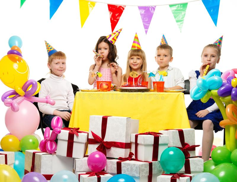 Group of children celebrating birthday. Croup of happy children celebrating birthday behind table royalty free stock images