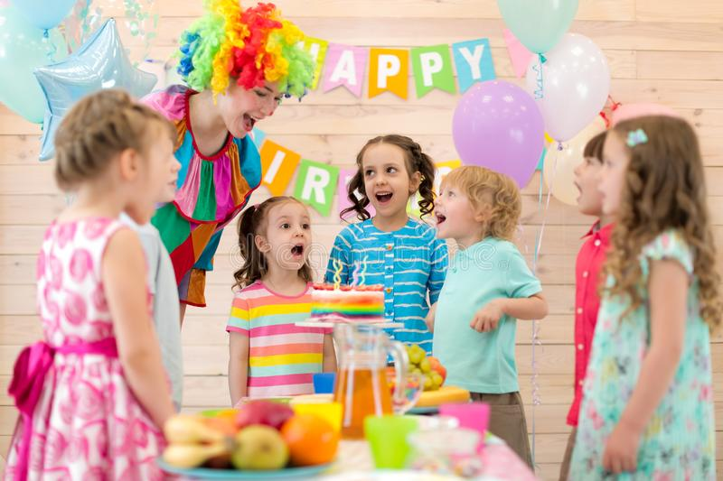 Group of children with clown blowing candles on cake at birthday party stock images