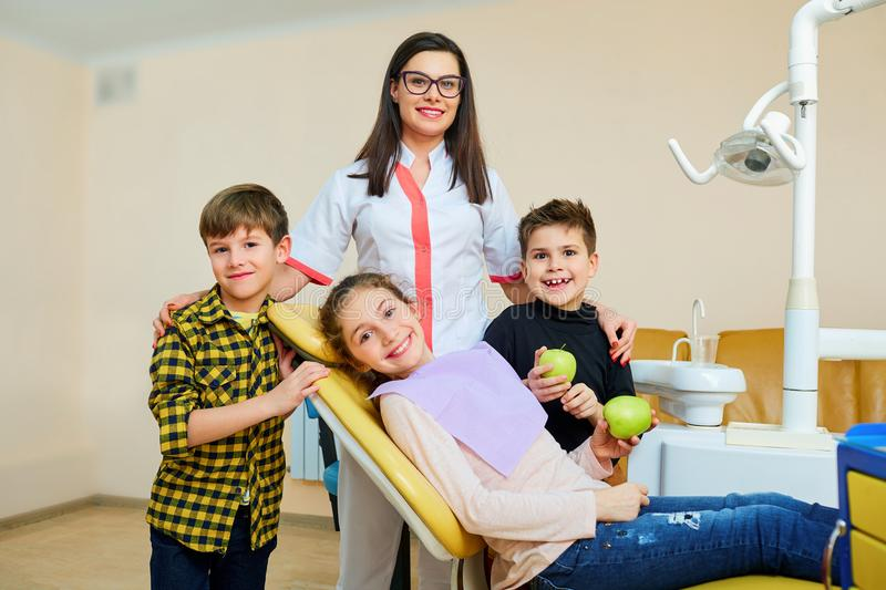 A group of children with a dentist a woman smiling. stock photos