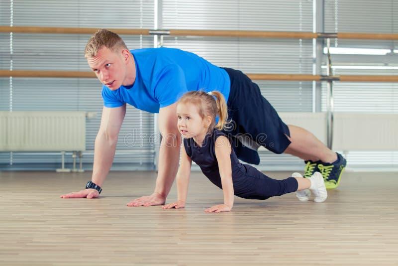 Group of children doing kids gymnastics in gym with nursery teacher stock image