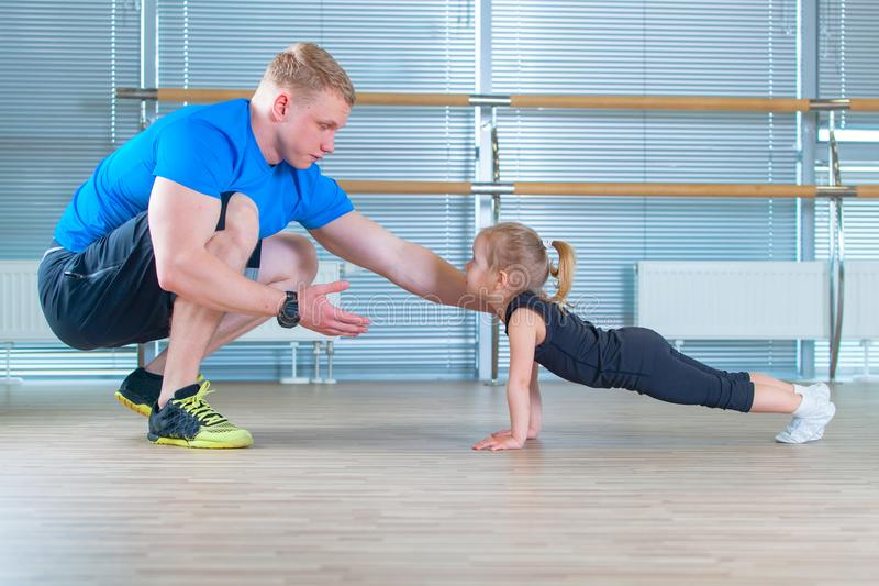 Group of children doing kids gymnastics in gym with teacher. Happy sporty children in gym. bar exercise. plank. stock photography