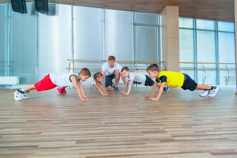 Group of children doing kids gymnastics in gym with teacher. Happy sporty children in gym. bar exercise. plank. royalty free stock images