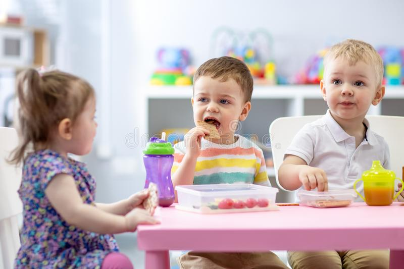 Group of children eating healthy food in daycare centre stock images