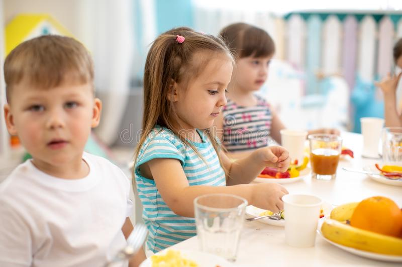 Group of children eating healthy food in daycare centre stock photo