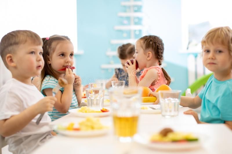 Group of children eating from plates in daycare centre stock photo