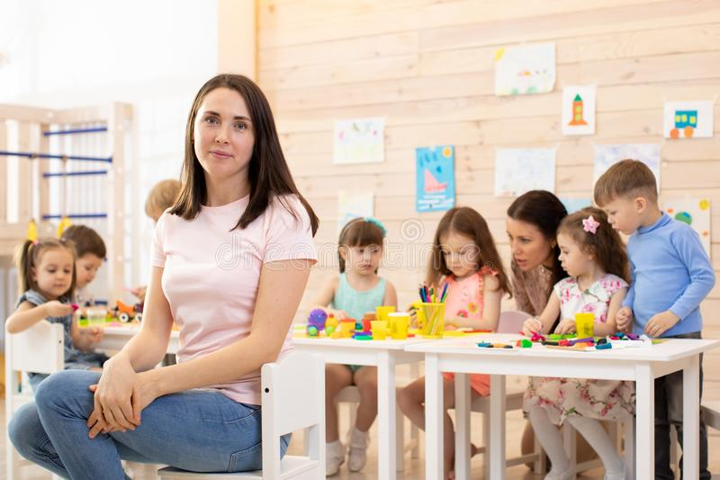 Group of kids and educator doing handcrafting together in classroom in kindergarten stock photos