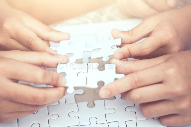 Group of children hand playing jigsaw puzzle together royalty free stock image