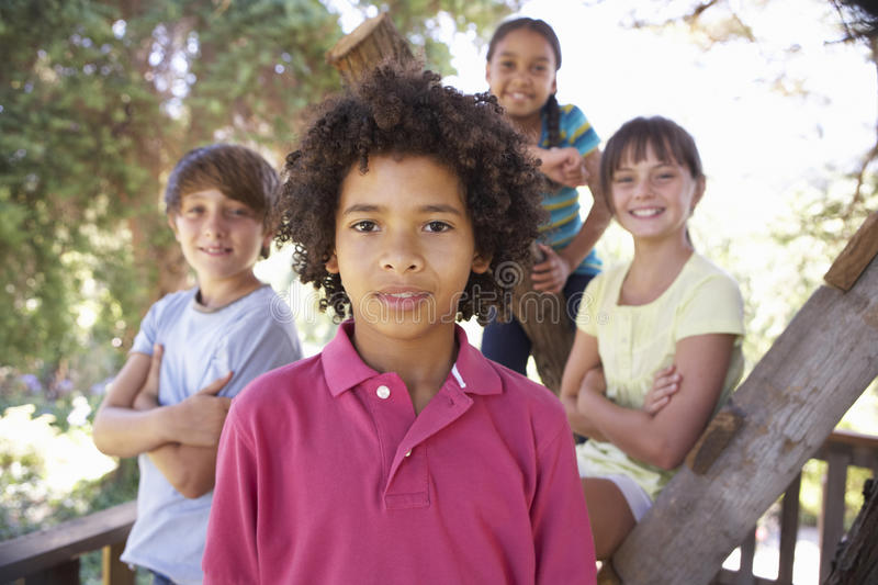 Group Of Children Hanging Out In Treehouse Together stock photos