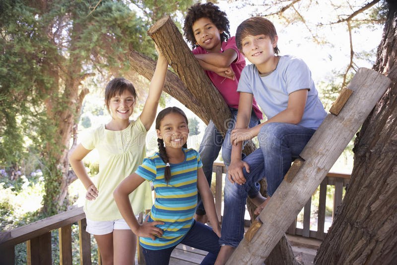 Group Of Children Hanging Out In Treehouse Together royalty free stock image
