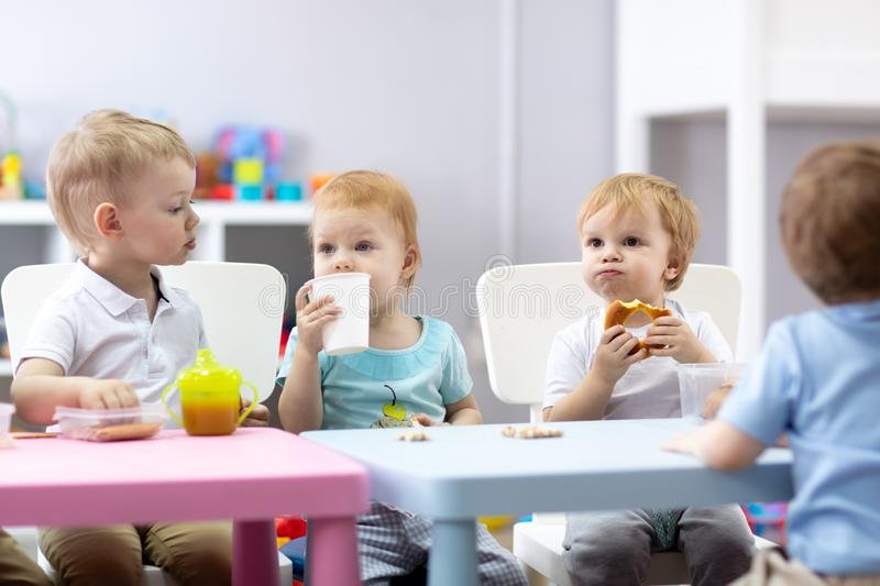 Group of children eating food in daycare centre royalty free stock image