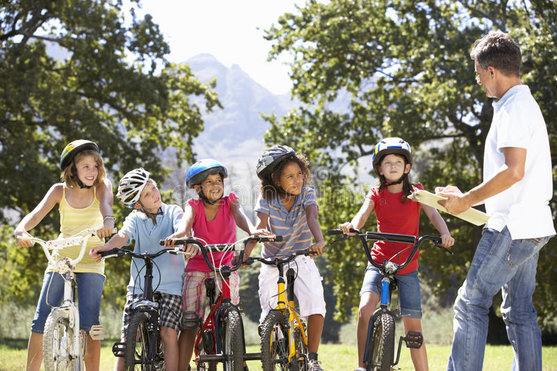 Group Of Children Having Safety Lesson From Adult Whilst Riding Bikes In Countryside stock photos