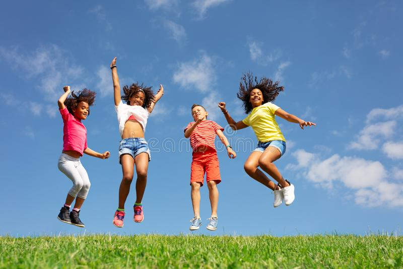 Group of children jump over blue sky and clouds stock image