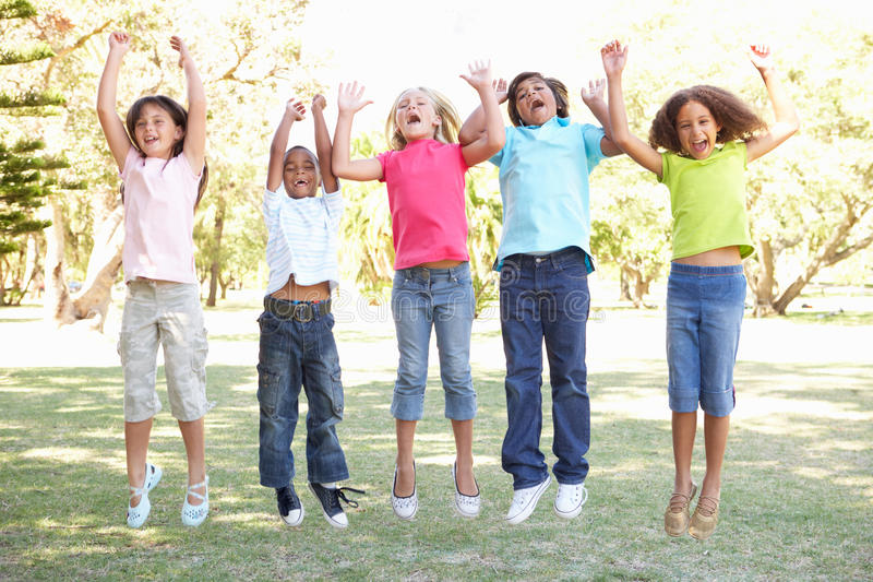 Group Of Children Jumping In Air In Park stock image