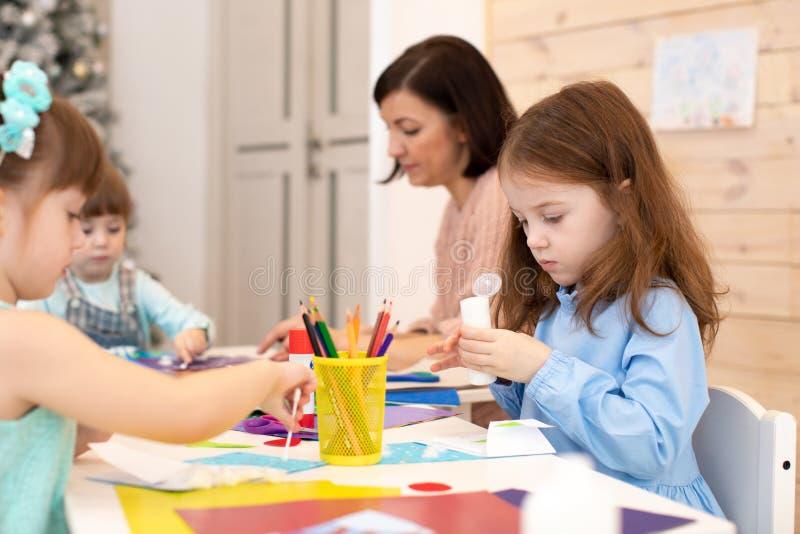 Group of children on lesson in kindergarten. Teacher helps kids hands working. Preschoolers activities in class royalty free stock photo