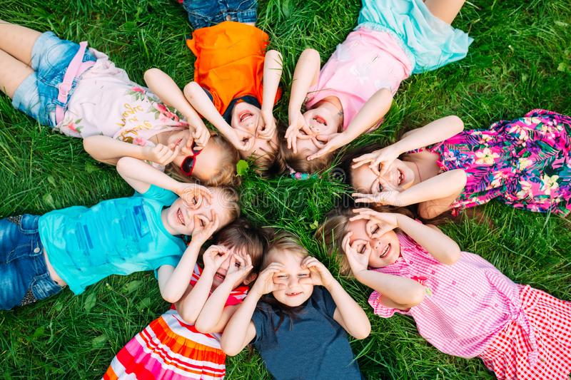 A group of children lying on the green grass in the Park. The interaction of the children. royalty free stock photography