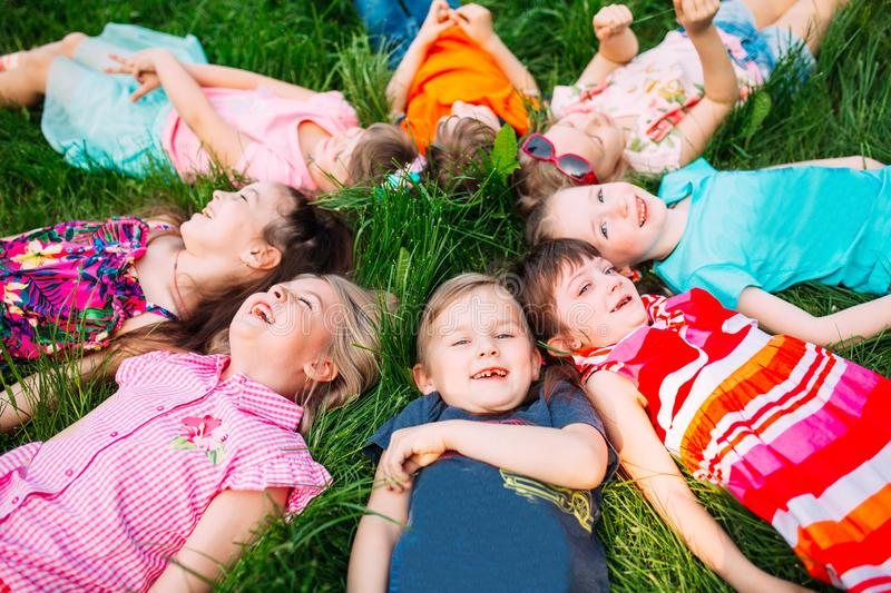 A group of children lying on the green grass in the Park. The interaction of the children. stock image