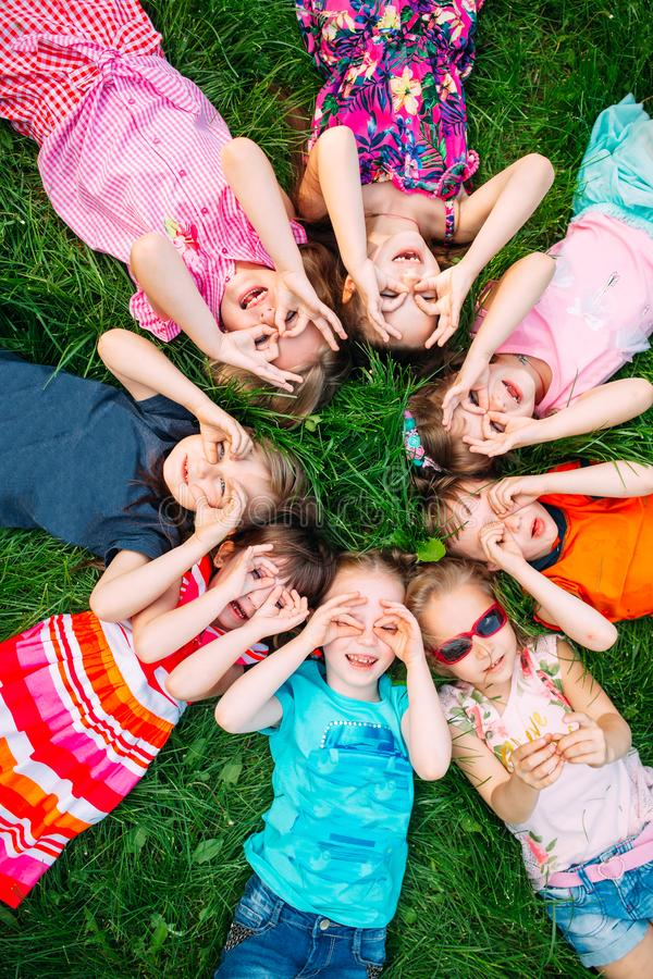 A group of children lying on the green grass in the Park. The interaction of the children. royalty free stock photos