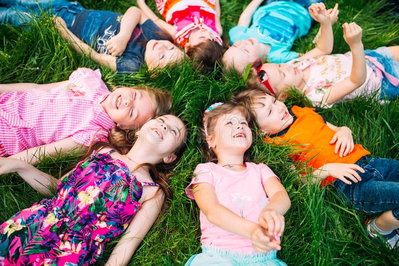 A group of children lying on the green grass in the Park. The interaction of the children. royalty free stock image