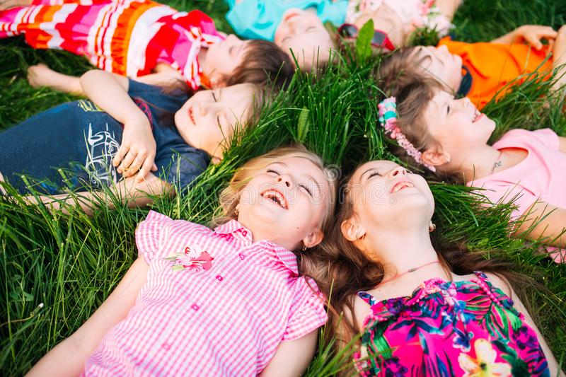 A group of children lying on the green grass in the Park. The interaction of the children. royalty free stock images