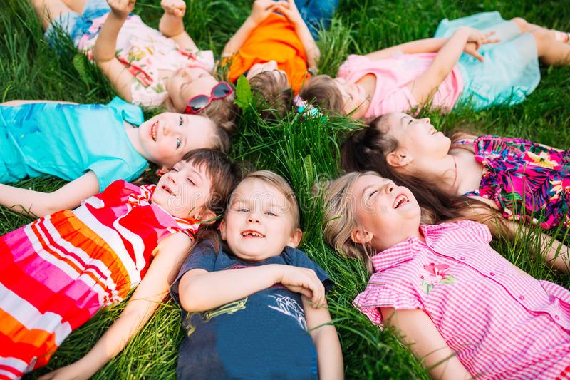 A group of children lying on the green grass in the Park. The interaction of the children. stock photography
