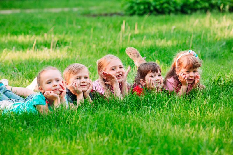 A group of children lying on the green grass in the Park. The interaction of the children. stock photo