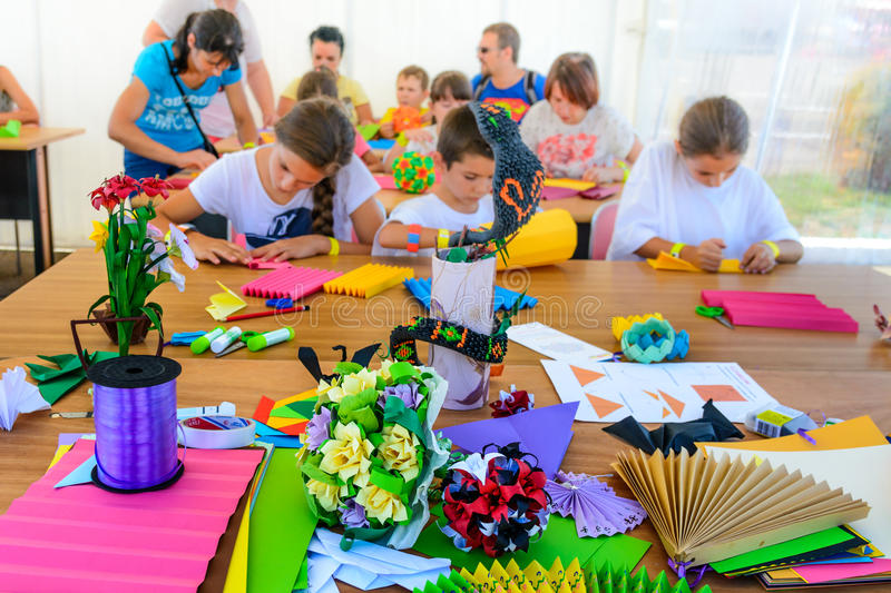 A group of children making crafts out of colored paper. Lifestyle scene of children making hand made goods together and having stock photos