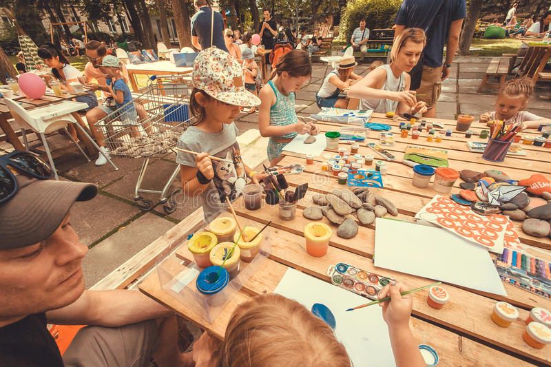Group of children with parents playing with paints and crayons on table of city playground stock images