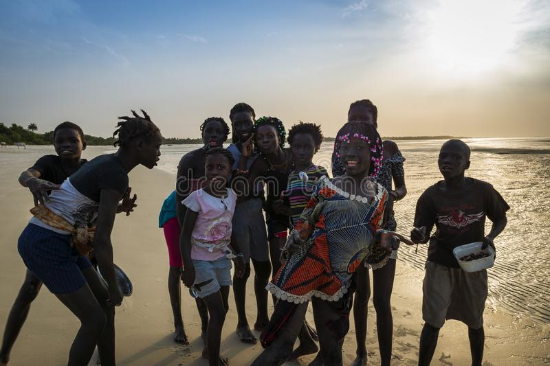 Group of children playing by the beach in the island of Orango at sunset, in Guinea Bissau royalty free stock images