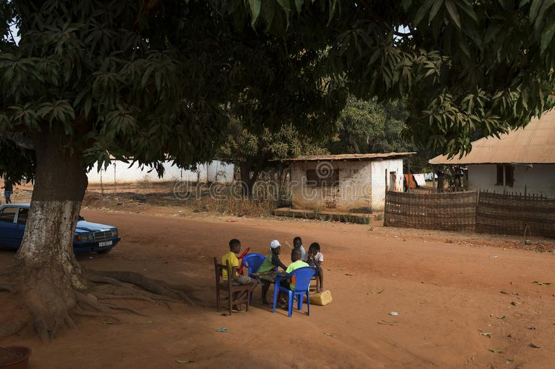 Group of children playing a game of checkers under a tree in the town of Nhacra in Guinea Bissau. Nhacra, Republic of Guinea-Bissau - January 28, 2018: Group of royalty free stock photography