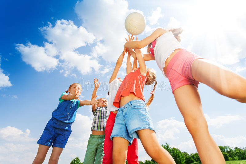 Group of children plays ball on a meadow royalty free stock images