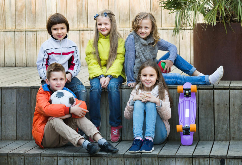 Group of children portrait with ball and skateboard. Group of ordinary cheerful children portrait with ball and skateboard outdoors stock photography