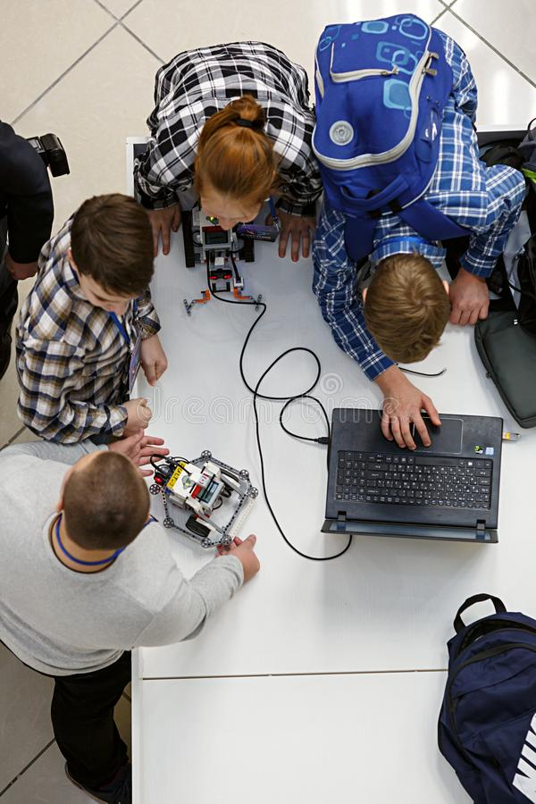 Group of children programming the robot at robotics competitions. stock image