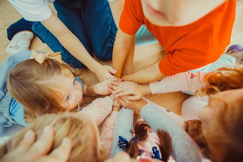 Group of children putting their hands together stock photos