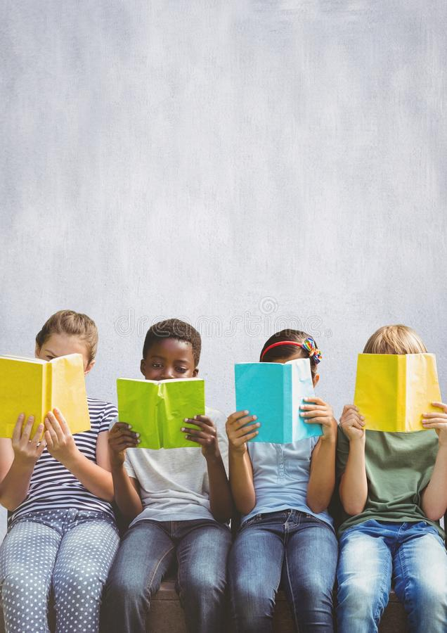 Group of children reading books in front of bright background stock images