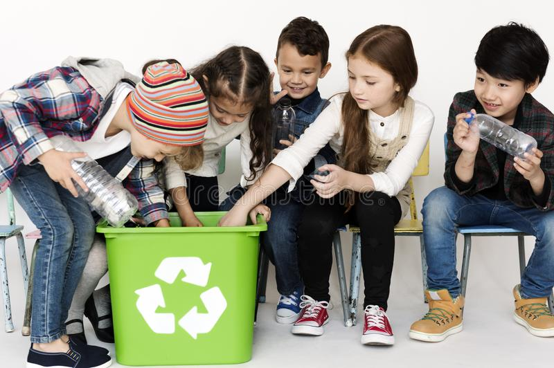 Group of children with a recycling symbol stock images