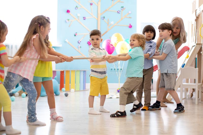 Group of children in a rope-pulling contest in kindergarten stock image