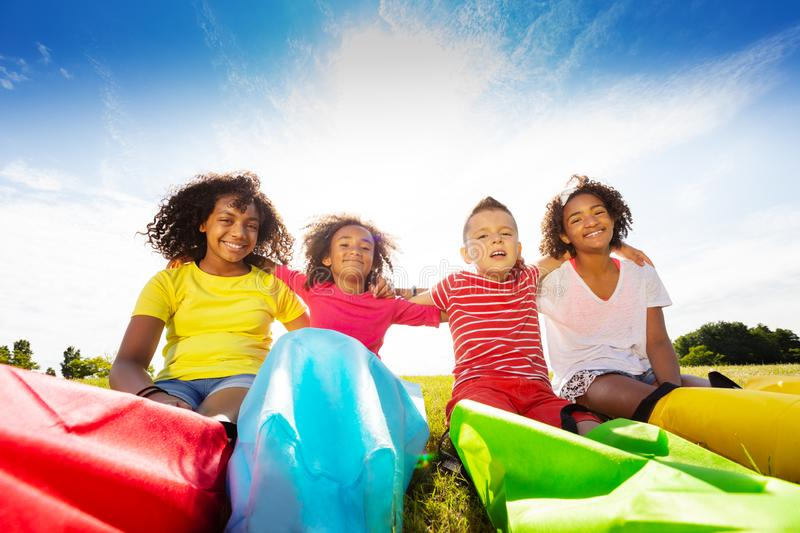 Group of children sit with race sacks on the lawn stock photo