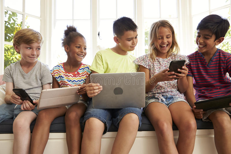 Group Of Children Sit On Window Seat And Use Technology stock photo
